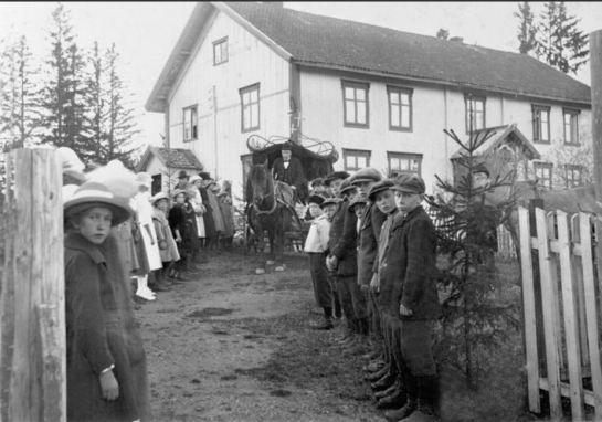 LIKVOGN MED HEST KJØRER UT AV GARDSTUNET - BARN OG VOKSNE STÅR OPPSTILT - 1920-TALLET